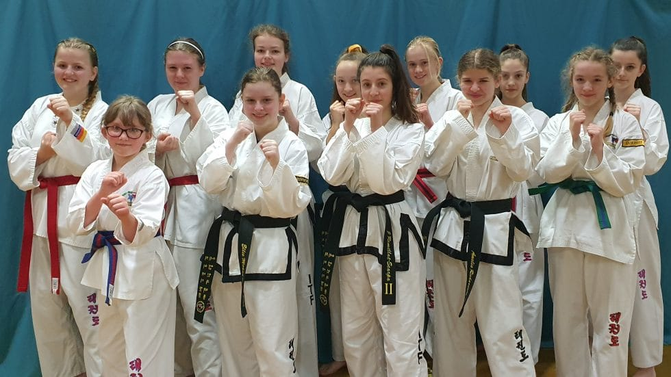 12 girls in fighting stance dressed in Taekwondo outfits