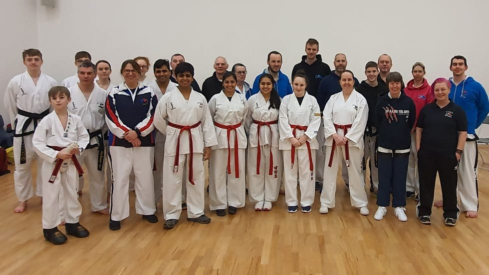 Group of Taekwondo students in outfit, umpires and referees in sport's clothes. Varied ages