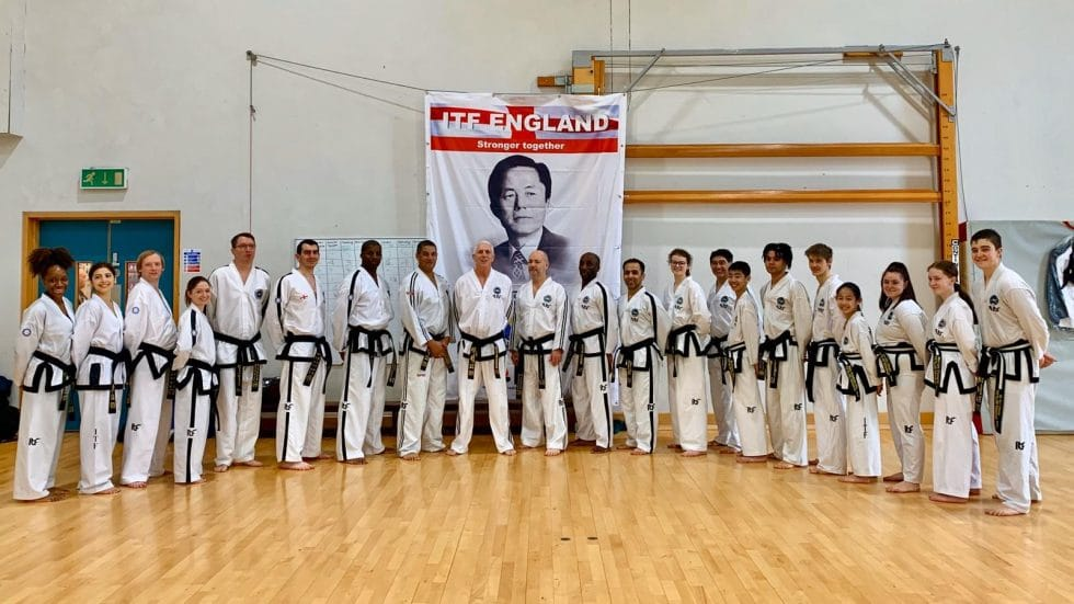 People in Taekwondo outfit posing in a semi-circle in front of a ITF England Stronger Together banner